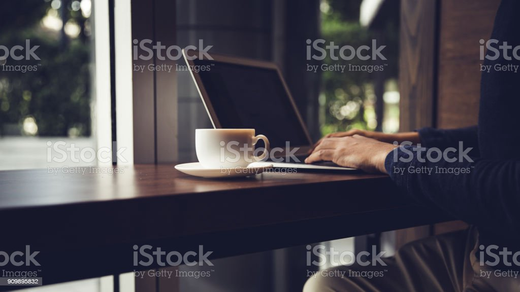 Selective focus of Side view laptop is on the work table in a conner...