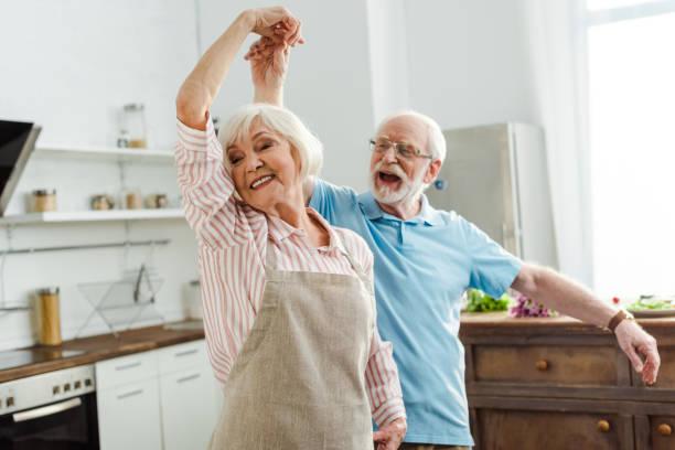 foco seletivo de casal sorridente dançando na cozinha - dançar - fotografias e filmes do acervo