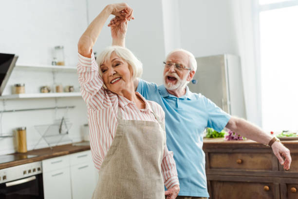 Selective focus of smiling senior couple dancing in kitchen stock photo