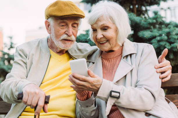 Selective focus of smiling senior woman holding smartphone near husband on bench in park stock photo
