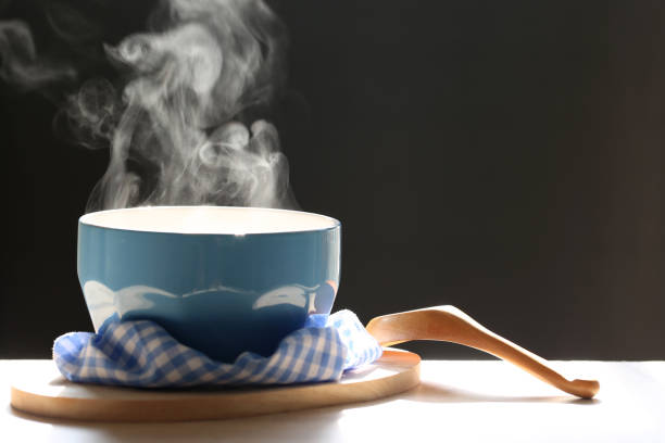 selective focus of smoke rising with hot soup in cup and spoon on dark background - sopa imagens e fotografias de stock