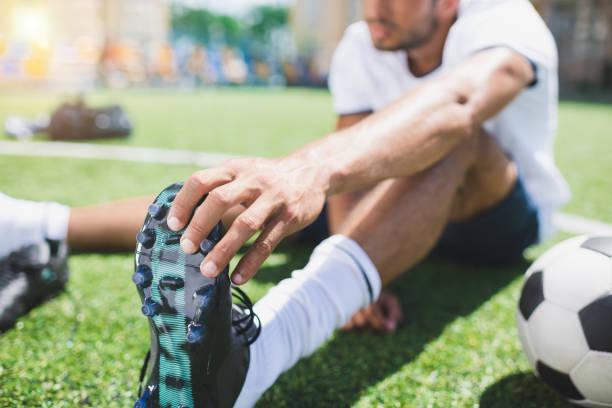 foco seletivo de jogador de futebol com chuteira sentado no campo - foto de acervo