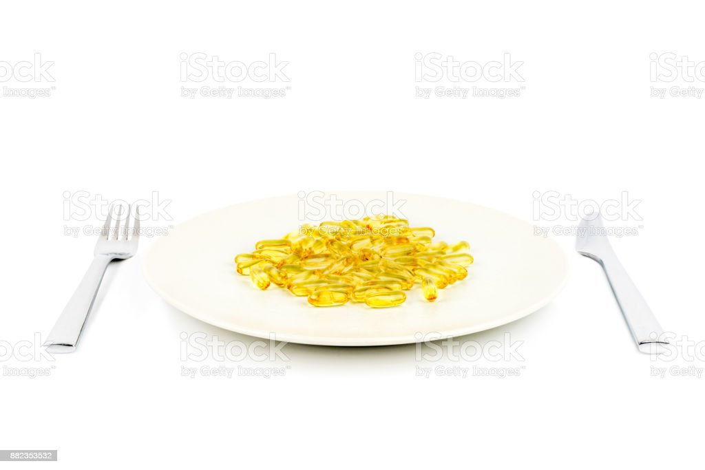 Selective focus of soft yellow capsules with healthy omega 3 fish oil on a dinner plate with knife and fork. stock photo