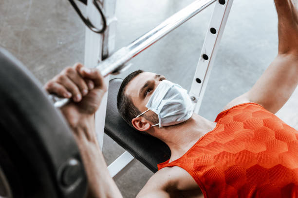 selective focus of sportsman in medical mask exercising with barbell in gym stock photo