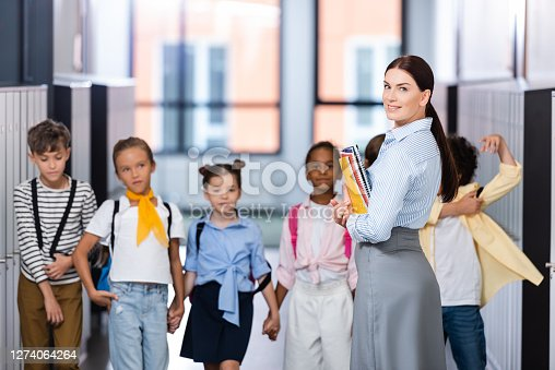 selective focus of teacher looking at camera while standing with multiethnic pupils in school corridor