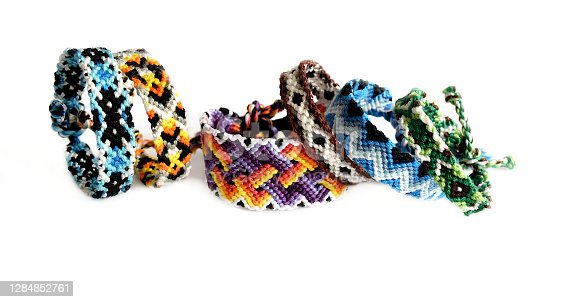 Selective focus of tied woven friendship bracelets with bright colorful patterns handmade of thread isolated on white background