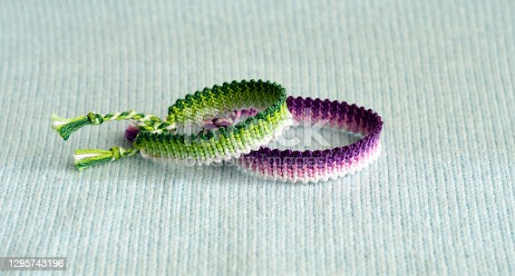 Selective focus of tied woven friendship bracelets with gradient pattern on blue woven background