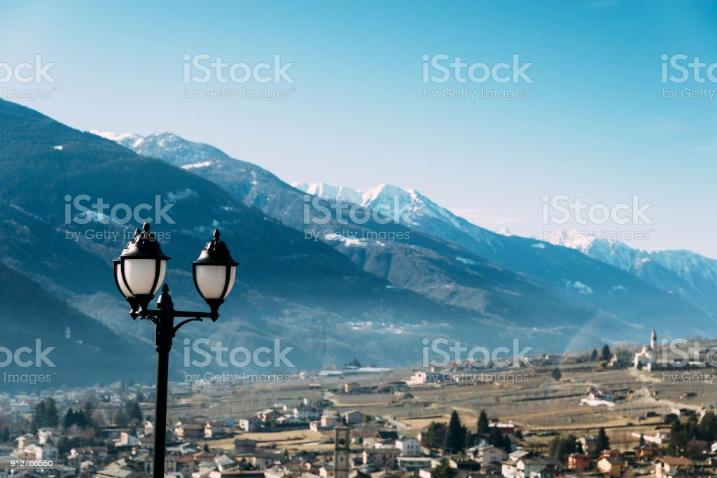 Selective focus of traditional lamppost and dining set table overlooking Sondrio, an Italian town and comune located in the heart of the wine-producing Valtellina region stock photo