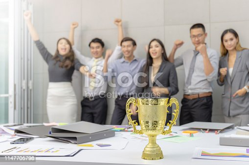 istock Selective focus of trophy with blurred success group of business people team meeting working in office 1147705798