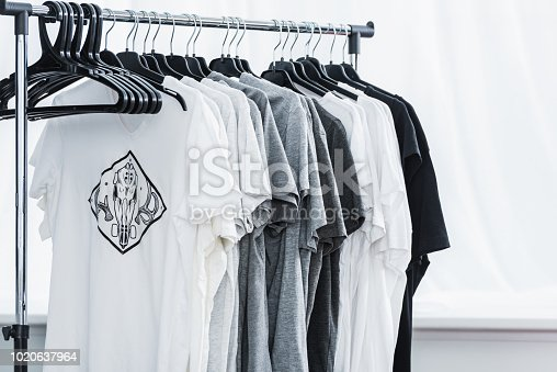 selective focus of t-shirts with print on hangers in clothing design studio
