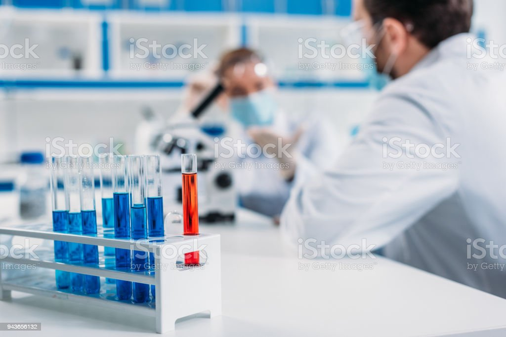 selective focus of tubes with reagents and scientists at workplace in lab stock photo