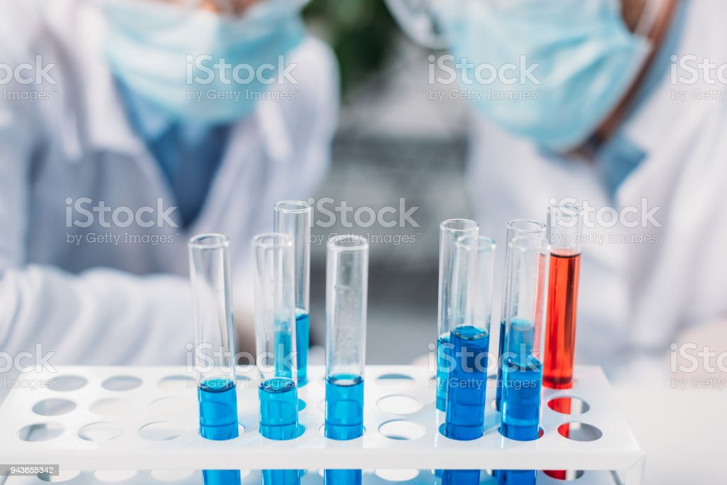 selective focus of tubes with reagents and scientists in medical masks stock photo