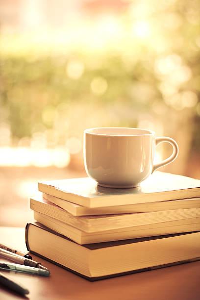 Geringe Tiefenschärfe weißen Kaffeetasse und Bücher Stapeln – Foto