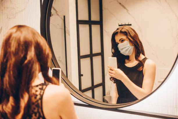 selectieve focus van vrouw in zwarte kleding en medisch masker dat foto in badkamers neemt - mirror mask stockfoto's en -beelden