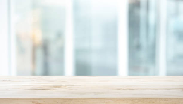 Selective focus of wood table top on white wall glass background stock photo