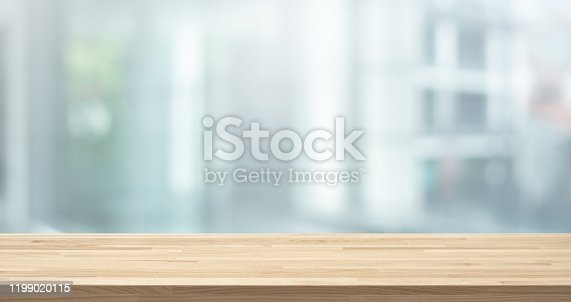 Selective focus of wood table top on white wall glass (big window) background.For montage product display or design key visual layout