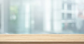 istock Selective focus of wood table top on white wall glass (big window) background 1199020115
