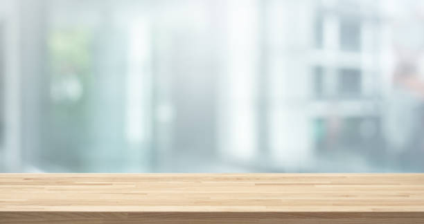 Selective focus of wood table top on white wall glass (big window) background stock photo