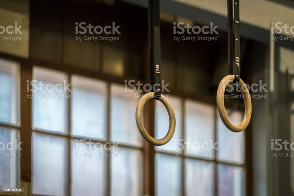 Selective focus of wooden gymnastic rings in front of a large window. stock photo