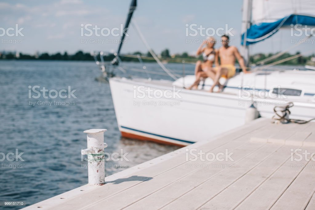 Selective Focus Of Wooden Pier And Young Couple On Yacht