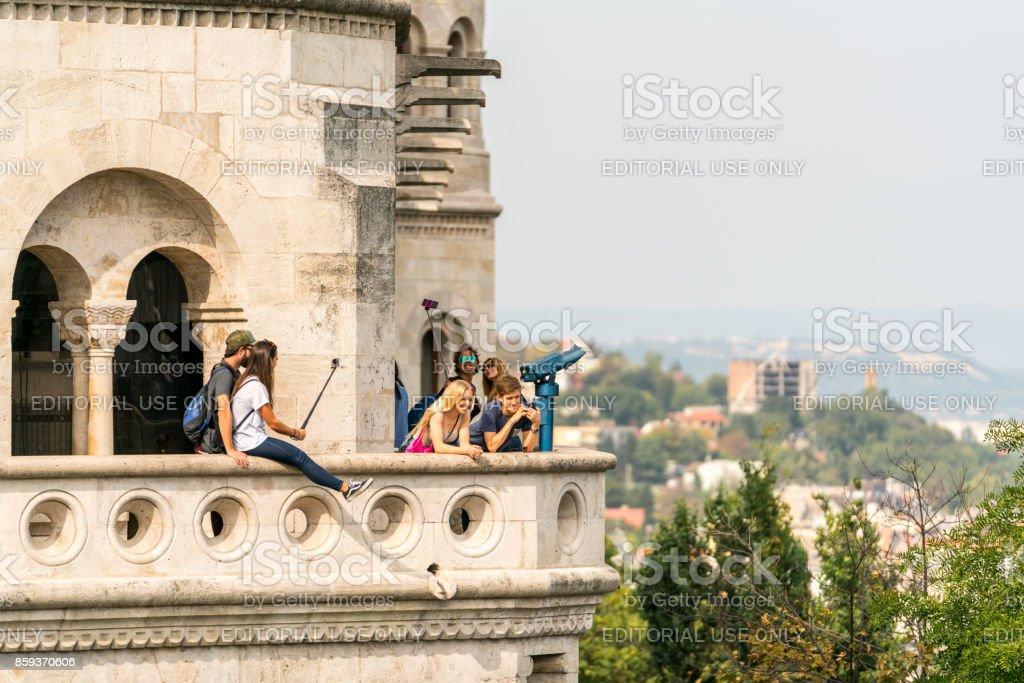 Selective focus of young tourists taking pictures at a viewpoint in Budapest with the city below. stock photo