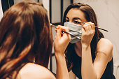 istock selective focus of young woman in medical mask and black dress applying eye shadow in bathroom 1253160478