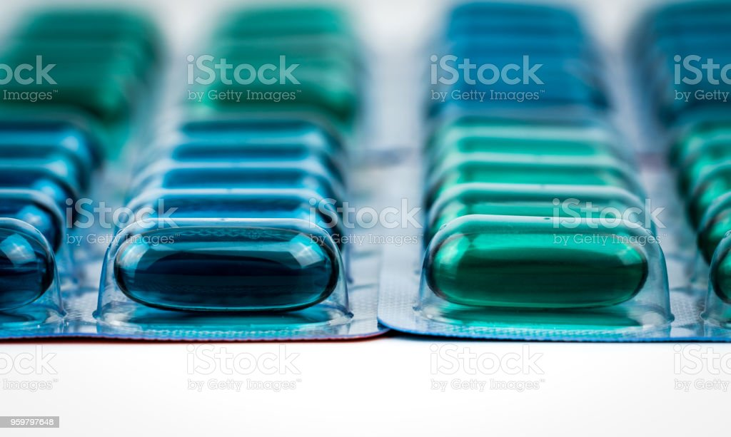 Selective focus on blue and green soft gel capsule pills in blister pack. Naproxen and ibuprofen (Nonsteroidal anti-inflammatory drugs) : Painkiller medicine. Pharmaceutical packaging industry. stock photo