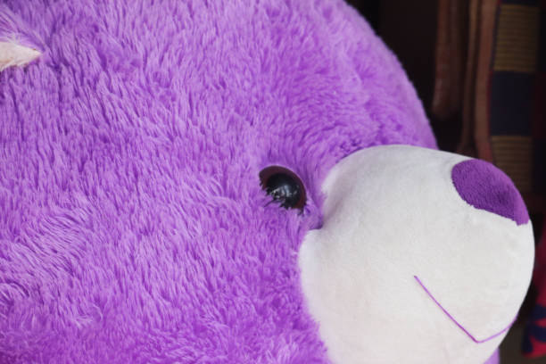 Selective Focus on Face Of Purple Colored Teddy Bear Selective Focus on Face Of Purple Colored Teddy Bear christmas teddy bear stock pictures, royalty-free photos & images