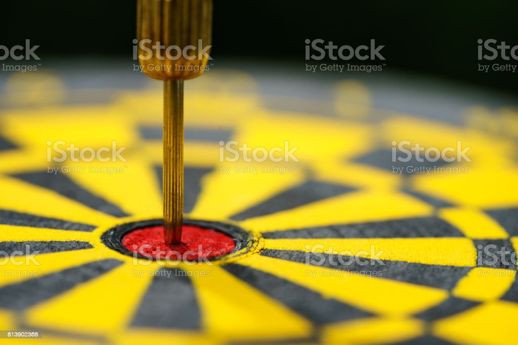 Selective focus on gold needle dart in the center of dartboard as Business goal or target concept stock photo