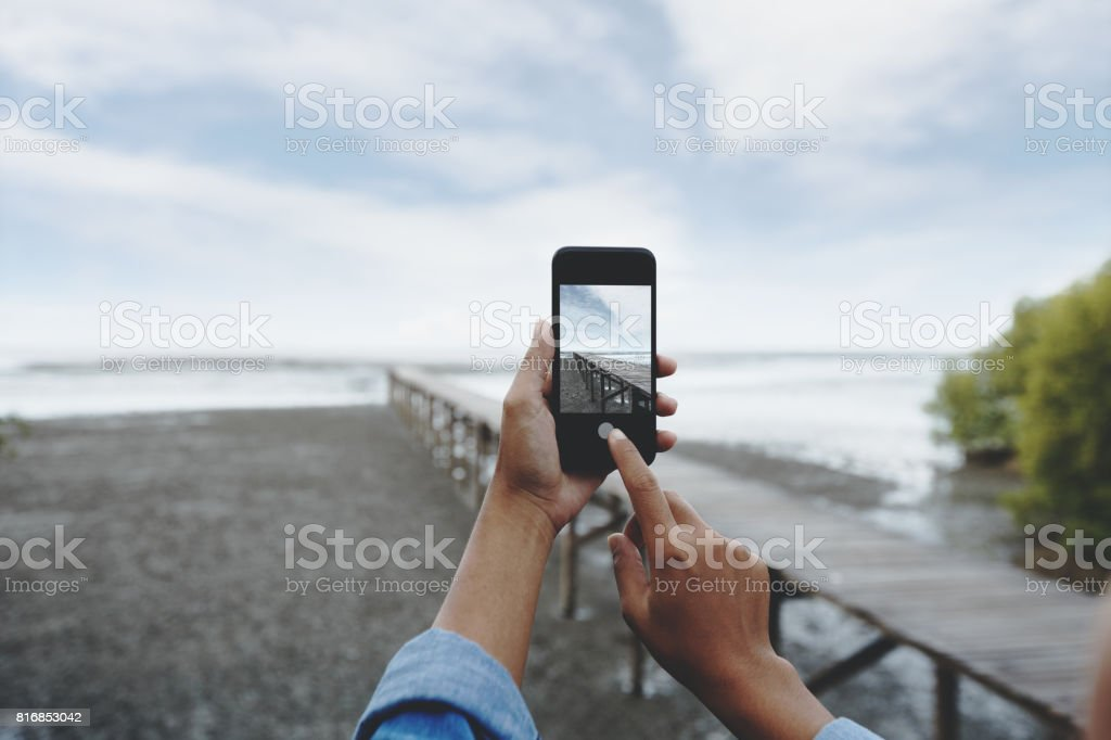selective focus on hand using smart phone taking landscape photo stock photo