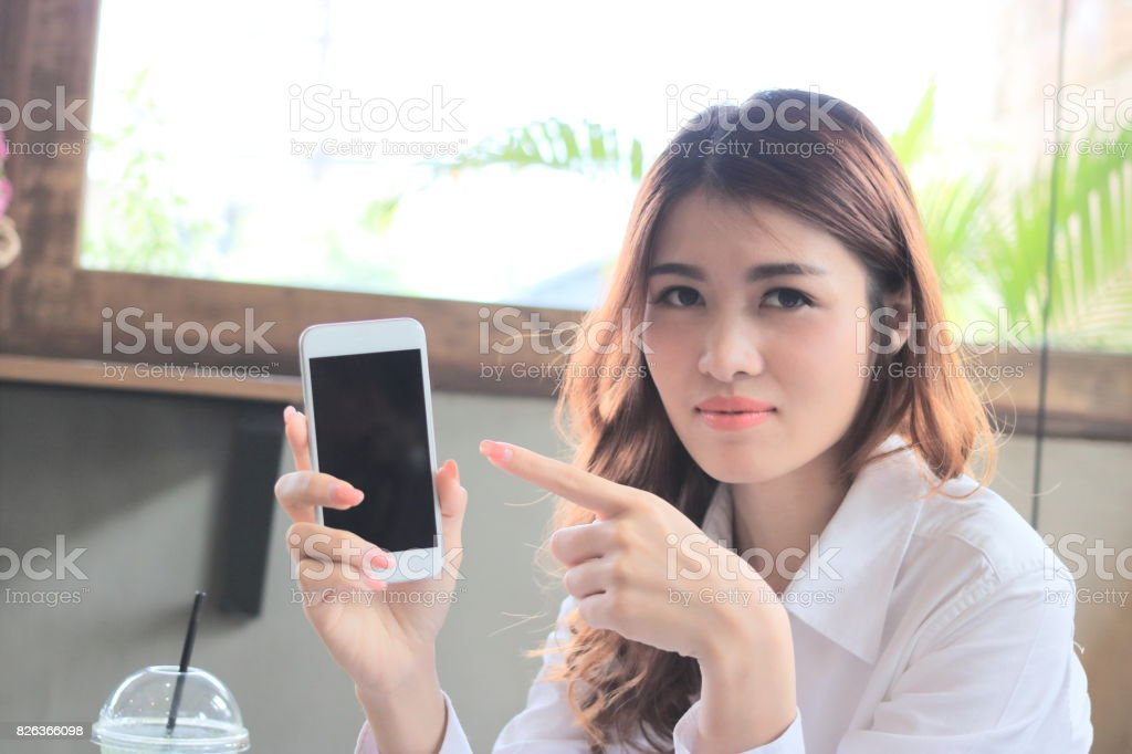 Selective focus on hands of attractive young Asian woman pointing finger on mobile smart phone screen in modern room background. stock photo