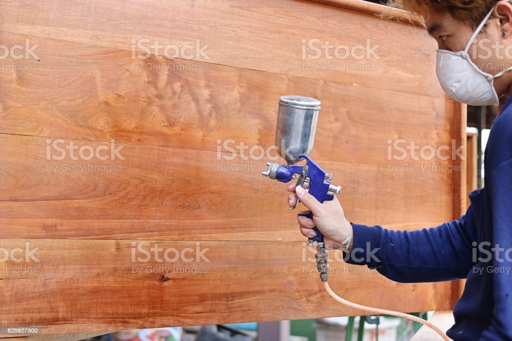 Selective focus on hands of industrial painter with safety mask painting a wooden furniture with spray gun in home workshop. Shallow depth of field. stock photo