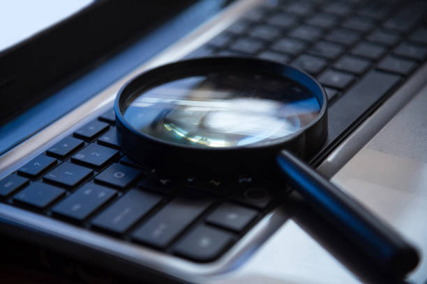 Selective focus on keyboard with magnifier searching concept in dark low key night tone stock photo