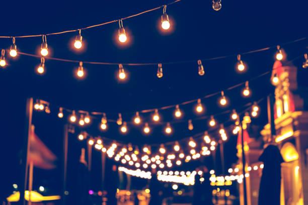 selectieve focus op lampen en bokeh achtergrond met ingang filter, abstracte achtergrond, vintage toon op nacht licht festival. - avondmarkt stockfoto's en -beelden