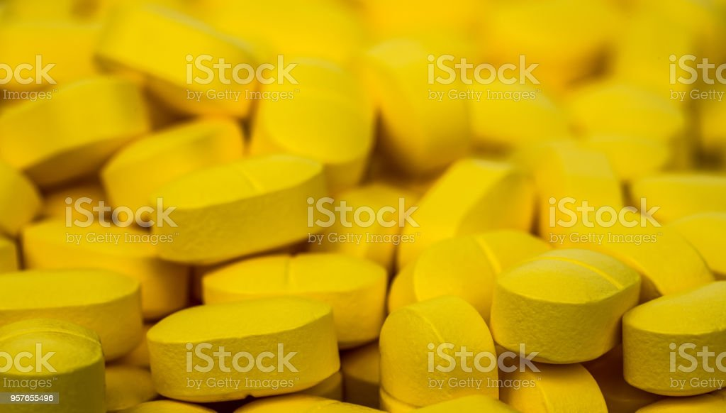 Selective focus on pile of yellow tablets pills . Ibuprofen tablets pills. Painkiller medicine for headache, fever and anti inflammatory. Pharmaceutical industry concept. Health policy and budgets. stock photo