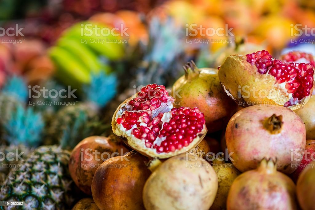selective focus on pomegranate and other fruits in morocco stock photo