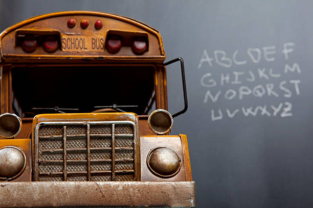selective focus on school bus with blackboard and alphabet stock photo