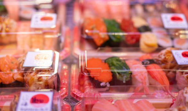 スーパーマーケットの棚にプラスチック製のボックスディスプレイに設定された寿司に選択的な焦点。持ち去る日本食。寿司配達事業使い捨てプラスチック容器で食べる準備ができて健康的� - スーパーマーケット 日本 ストックフォトと画像