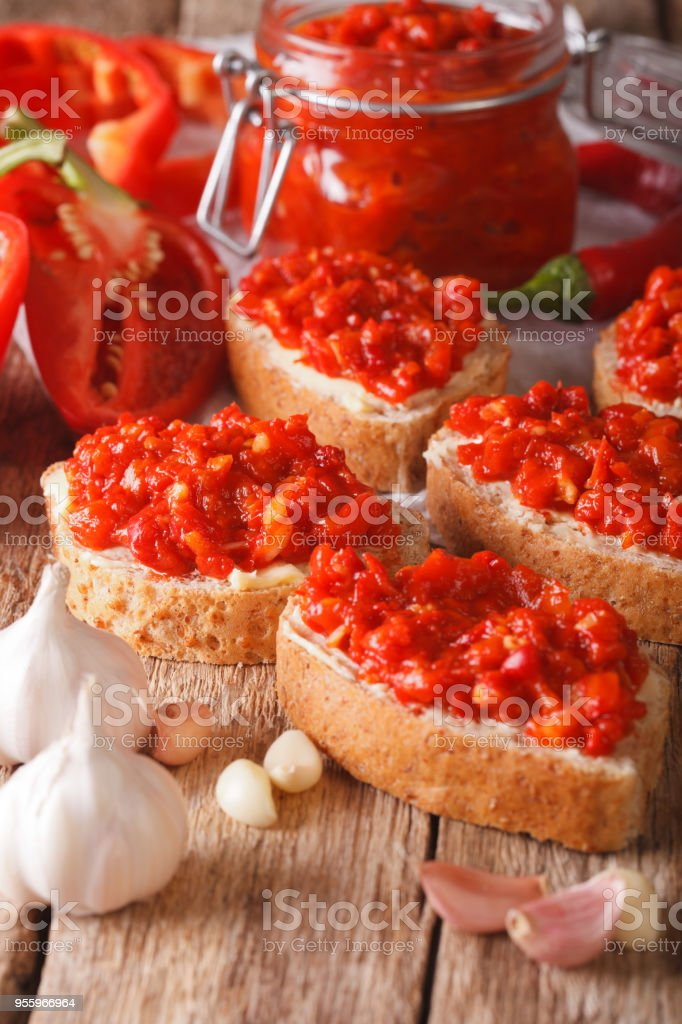 Selective focus on the ajvar on whole grain bread closeup. Vertical stock photo