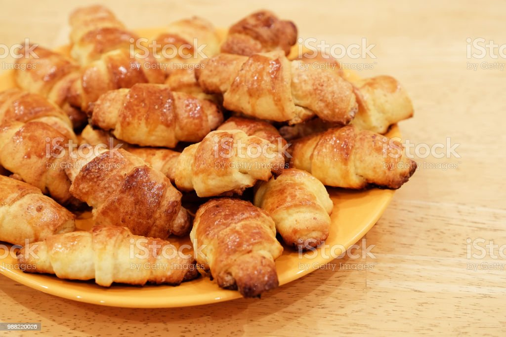 Selective focus on the front small croissant. Small croissants, homemade cakes. Blurred background. stock photo