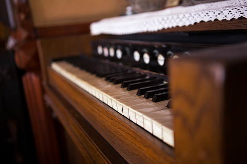 Selective focus on the keyboard on an old rustic piano. There are lace tablecloths on the piano.