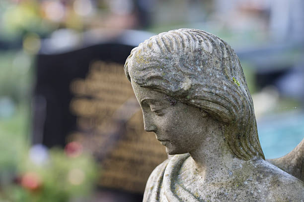 stone angel in churchyard with soft paster bokeh - whiteway stock photos and pictures
