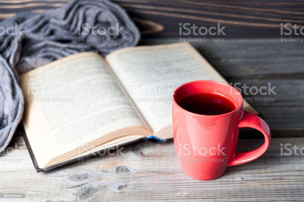 selektiven Fokus Foto von grauen gemütliche Schal mit Tasse Kaffee oder Tee und offenes Buch auf einem Holztisch. – Foto