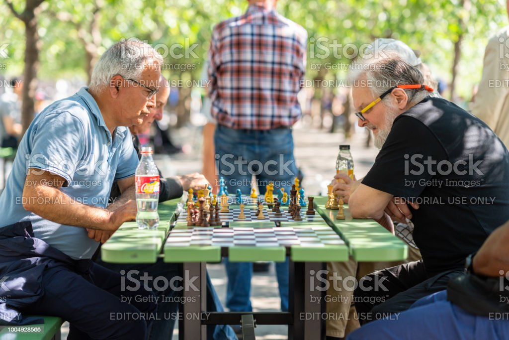 Selective focus side view of older men playing chess in a city square. stock photo