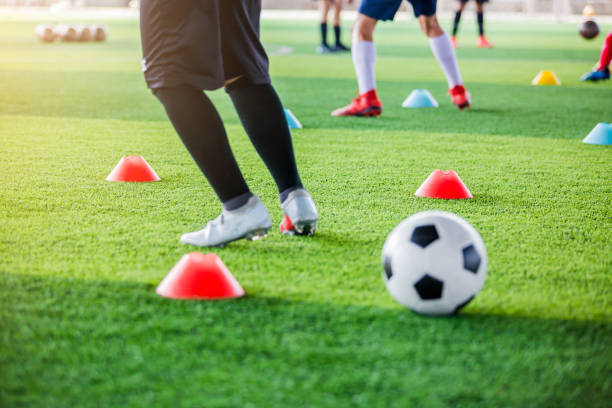 selective focus to red marker cones with blurry soccer ball and kid soccer player Jogging and jump between cone markers stock photo