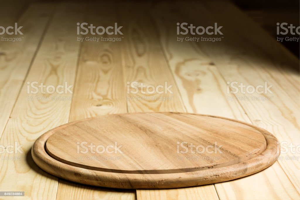 selective focus Wooden pizza plate with wooden background stock photo