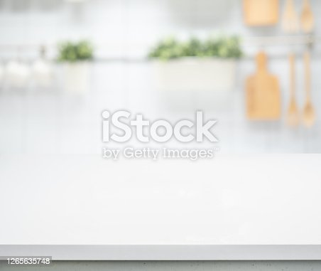 Selective focus/White wood table top on blur kitchen counter (room)background.For montage product display or design key visual layout.