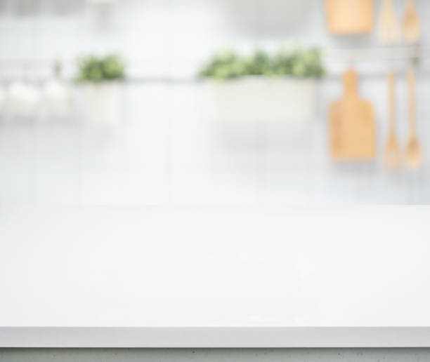 Selective focus/White wood table top on blur kitchen counter stock photo