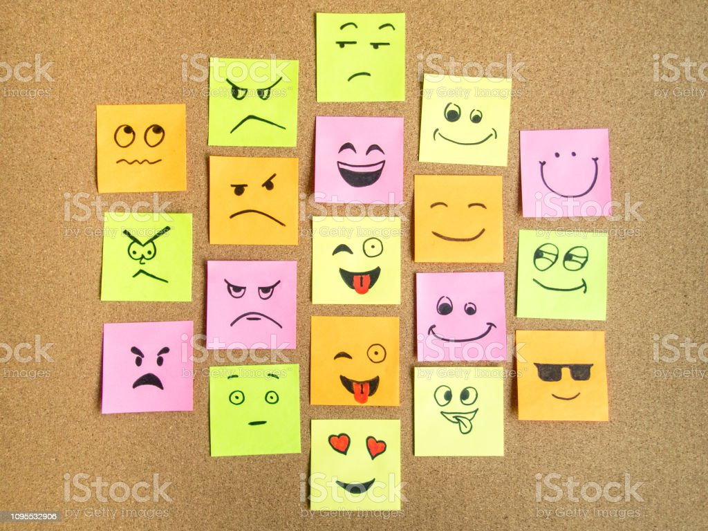 self adhesive office notes with different face expression on cork...