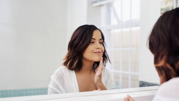 Self care, another form of love Shot of an attractive young woman going through her morning beauty routine in the bathroom routine stock pictures, royalty-free photos & images